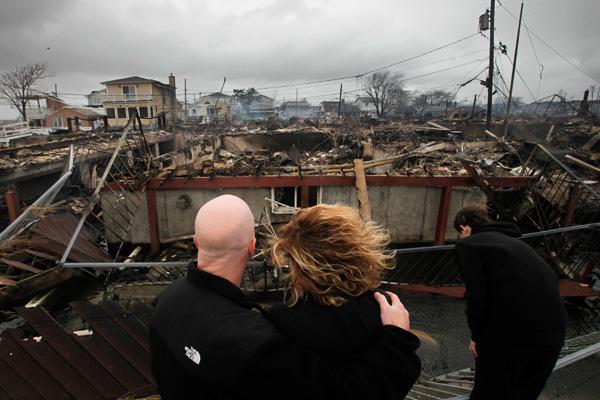 Casal observa ruínas de residências em Ocean Avenue, na área de Breezy Point, em Nova York, após passagem do furacão Sandy