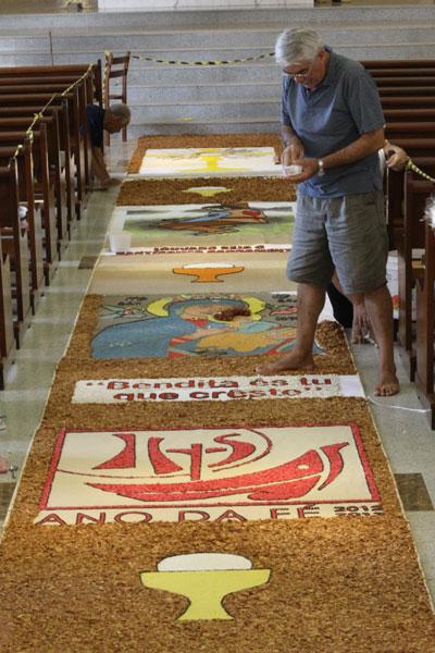 Os tapetes coloridos tradicionais na celebração de Corpus Christi trazem a mensagem do Ano da Fé