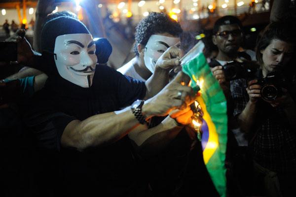 Integrante do grupo Black Bloc ateia fogo na Bandeira Brasileira em dia de protestos no Rio