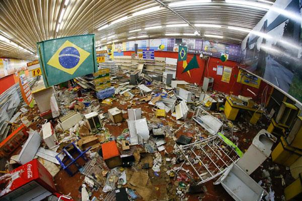 Técnicos fazem perícia em uma das lojas do Supermercado Arco Íris, saqueada na quarta-feira