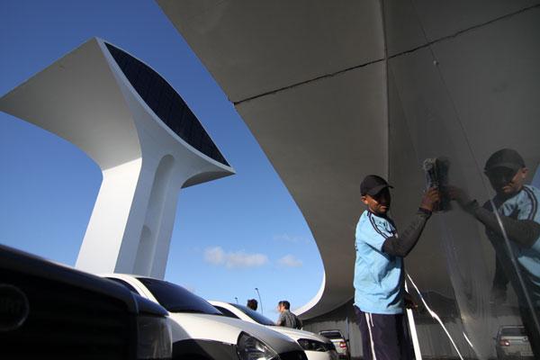 Operários trabalham na limpeza da estrutura que tem a assinatura do arquiteto Oscar Niemeyer