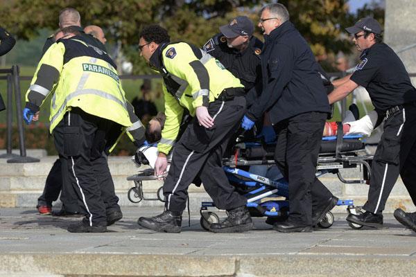 Socorristas transportam um dos feridos durante tiroteio no Memorial Nacional da Guerra