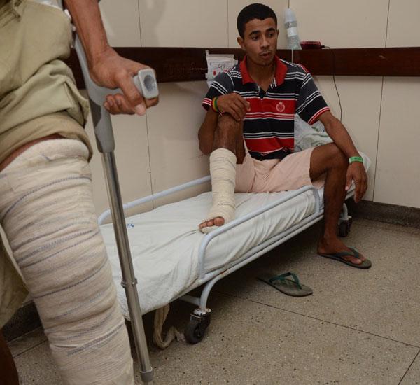 Eduardo Paulino (sentado) espera por cirurgia no corredor do HWG