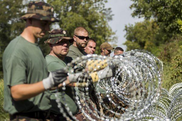 Soldados húngaros montam cerca temporária com serpentina na fronteira com a Croácia