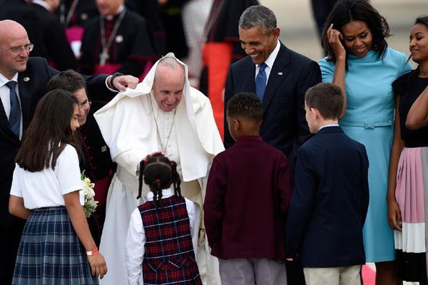 Recebido por Obama e família, papa Francisco cumprimenta crianças na base áerea de Maryland