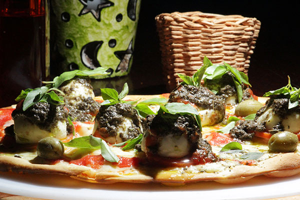 """Pizza """"Saturno"""" é feita com mussarela de búfala, pesto de azeitonas pretas e manjericão"""