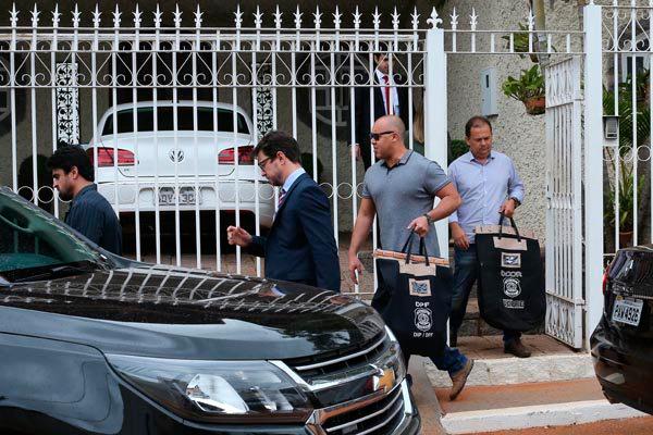 Policiais federais deixam a residência do ex-senador Luiz Otávio e carregam malotes após cumprimento de busca e apreensão