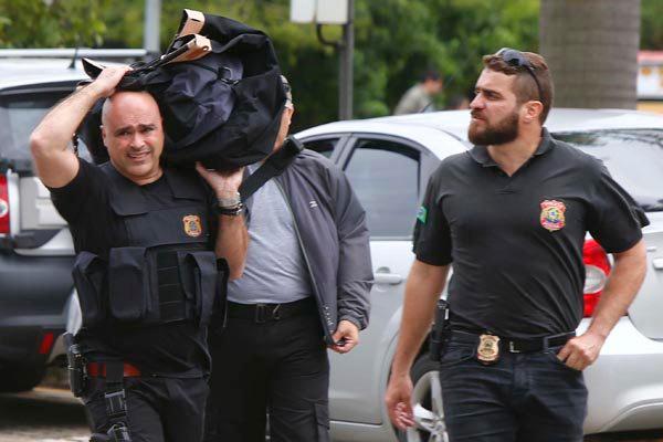 Policiais chegam, após o cumprimento do mandado de busca, com material apreendido na sede da PF
