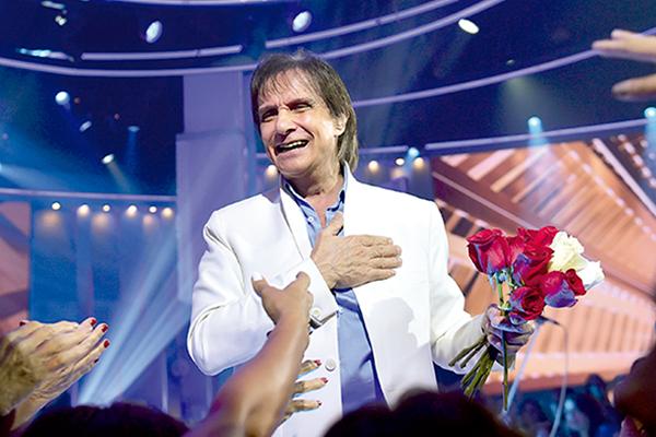 Roberto Carlos mantém o ritual de jogar as  flores para a plateia, ao final do show