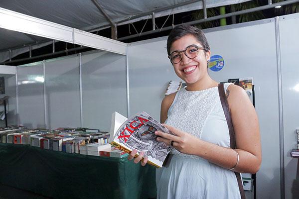 Anna Clara descobre os títulos dos autores que estão no Festival