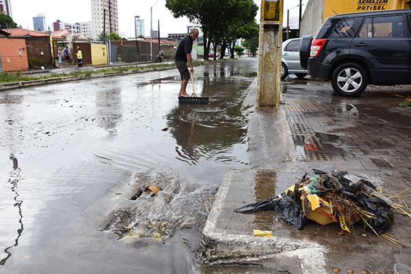 Av. Capitão-Mor Gouveia: morador retira lixo de galerias, para que a água empoçada possa escoar