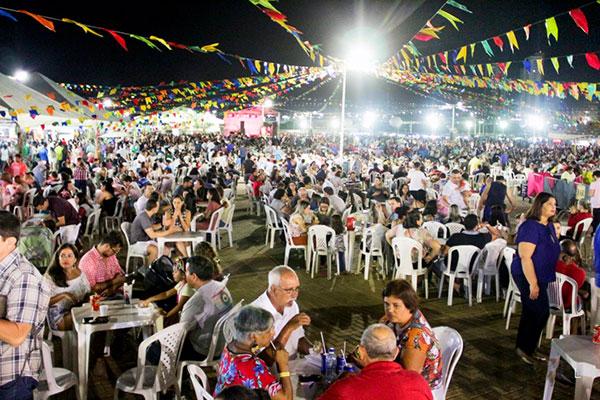 Pátio decorado e barraquinhas de comidas variadas e regionais para o público apreciar antes dos shows
