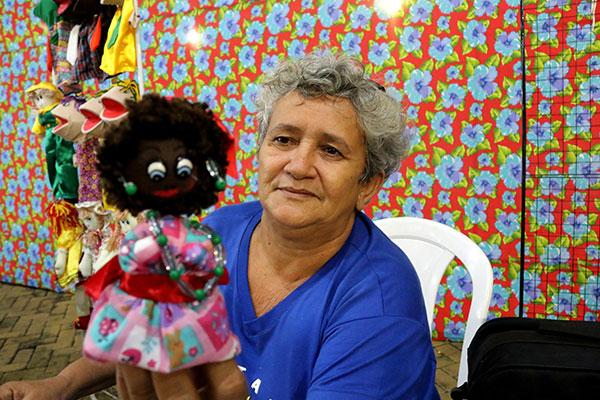 Inês de Assis e sua Catarina, um dos  bonecos de pano à venda. Ela procurou se diferenciar investindo em figuras do folclore nordestino