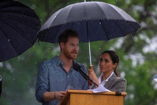 Grávida, Meghan Markle quebra protocolo e segura guarda-chuva para príncipe Harry