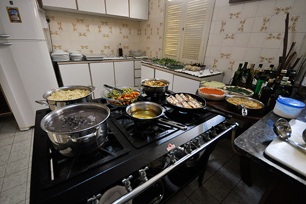 Na casa de Véscio Lisboa, a experiência caseira completa: o chef prepara a comida e o cliente se serve direto das panelas