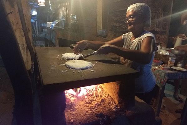 Dona Sônia Vieira prepara a tapioca em um dos fornos de cimento com fogo à lenha por baixo – um para as tapiocas e outro para o café