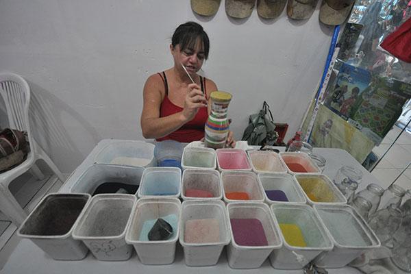 No Mãos de Arte, a artesã  Eridan Fagundes mostra sua experiência de 38 anos na arte de esculpir garrafinhas de areias coloridas naturais. Está no local há dois anos, criando as peças na hora