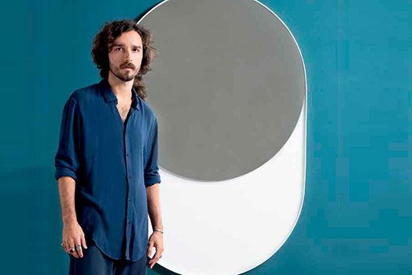 Filipe Bulhões em foto da revista Kaza como um de seus trabalhos, o Vesica Mirror, espelho que parece flutuar da parede. O Cruzeiro de Pipa, inspirado no monumento praiano, e a escultura Faces