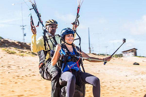 Na Costeira, a prática de parapente é em voo livre ou a motor. A apresentadora Anne Marjorie experimenta ao lado de instrutor