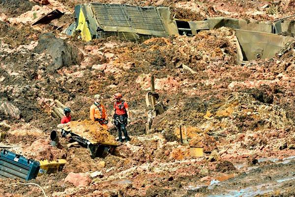 Bombeiros tentavam, poucas horas após a tragédia, iniciar o trabalho de buscas por vítimas na área devastada pelo rio de lama