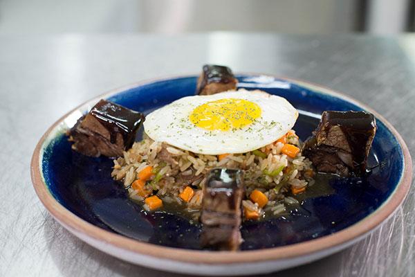 Costela no bafo é servida com arroz do próprio molho, jerimum e ovo frito