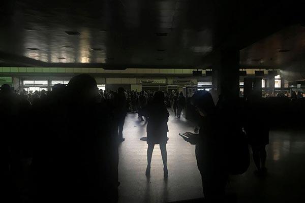 Passageiros durante um apagão no aeroporto internacional Simon Bolívar em Caracas, Venezuela