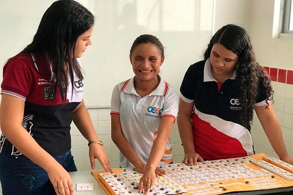Laine Sousa e Aysla Ferreira colaboram com Jéssica Dayane (C) produzindo tabela periódica para as aulas de Química