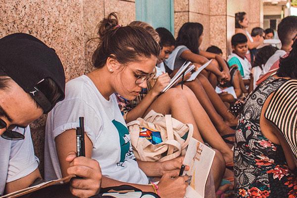 Acompanhados de curiosos, artistas se acomodam numa escadaria para observar os melhores cenários de Ponta Negra