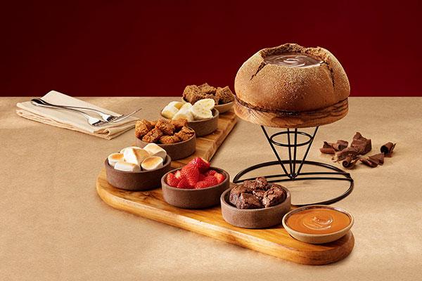 Em vez de usar o tradicional rechaud, o mix de queijos e a calda de chocolate são servidos no icônico pão australiano