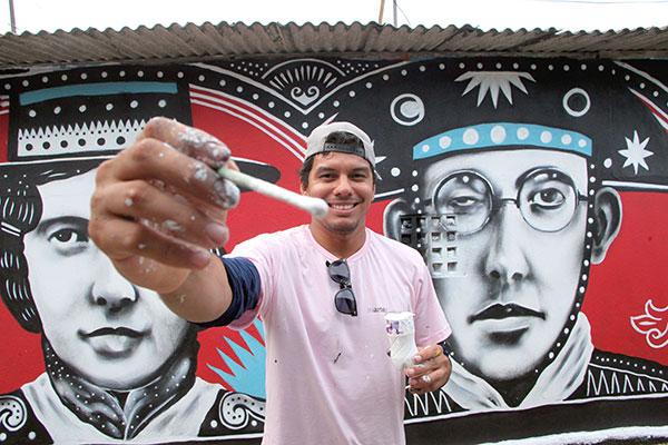 O artista Rocha pinta enquanto papeia com a moradora