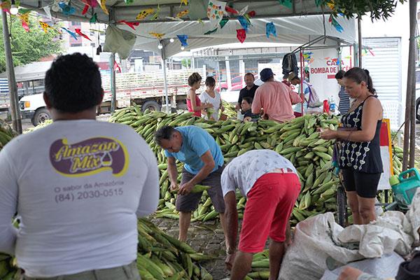 Comerciantes acomodam seus produtos na feirinha do milho na área externa da Central de Agricultura Familiar