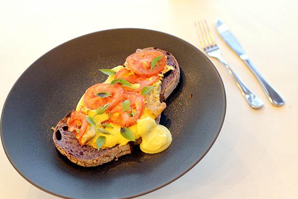Tostada: Fatia de pão de longa fermentação, colorida naturalmente, com muçarela de castanha de caju, tofu, tomate