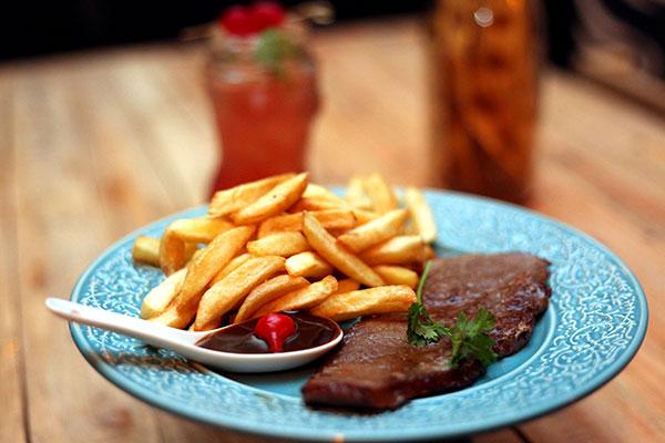 Do menu de petiscos, o bife de alcatra com batatas-fritas e molho