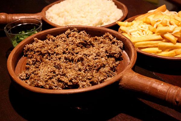 Carne de sol na nata é preparada no pilão e servida de maneira farta, para compartilhar à mesa
