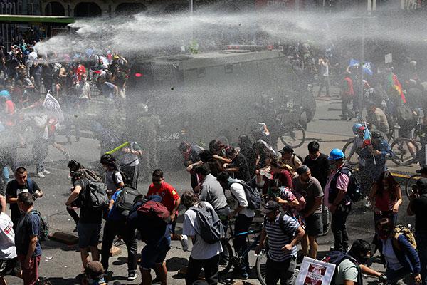 Manifestantes e policiais entram em confronto durante protesto nas ruas de Santiago