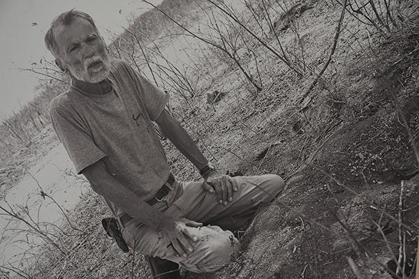 Oswaldo Lamartine em raro registro imagético de 1999, na fazenda Acauã: De joelho e e cabeça baixa, sua foto favorita. Ao lado, o acervo organizado por Leide Câmara e Humberto Hermenegildo