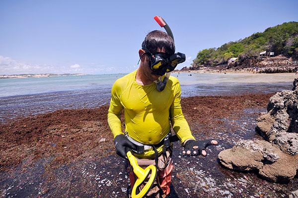Maykel vasculha as areias de Ponta Negra atrás de metais perdidos