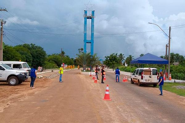 Vigilância da Saúde e voluntários atuam na barreira da entrada da cidade para evitar propagação do vírus. Decreto prevê multa por descumprimento