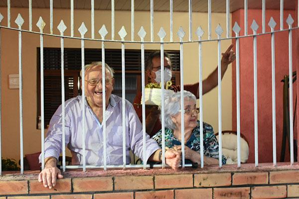 Da varanda da casa, ao lado da mulher Olindina, ele via os carros passando com faixas e balões