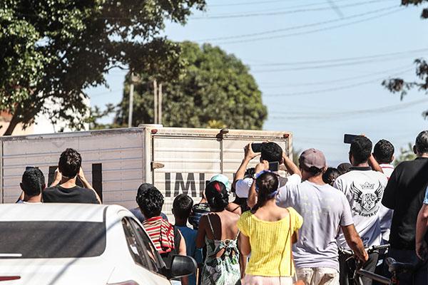 Populares registram com celulares a passagem do veículo do Instituto Médico Legal transportando o corpo de Lázaro Barbosa