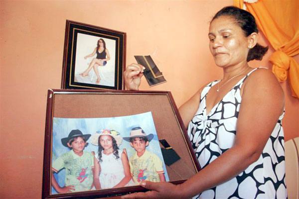 Dona Maria Aparecida mostra porta-retrato que quebrou após cair durante tremor