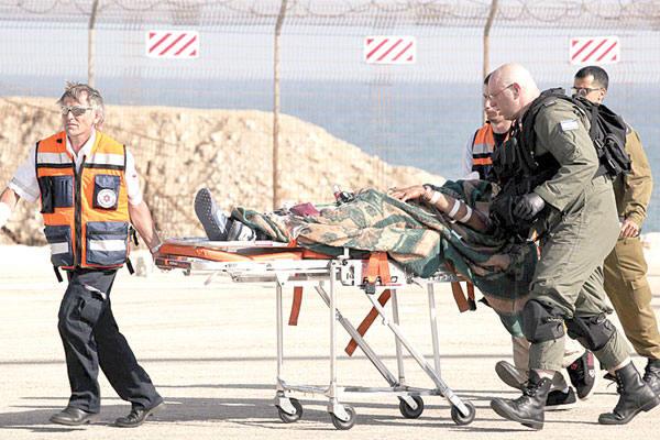 Médicos israelenses socorrem em Haifa, Israel, vítima de ataque ocorrido em navio em Gaza. País justificou a ação dizendo que grupo teria atacado  soldados durante abordagem