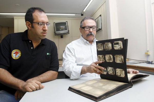 Frederico e Maranhão manuseam álbum de fotografias do radiotécnico Sternberg,  que serviu nas forças aéreas americanas em Natal