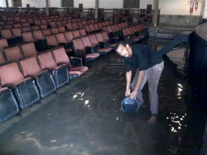 Funcionário tenta retirar água acumulado no TAM