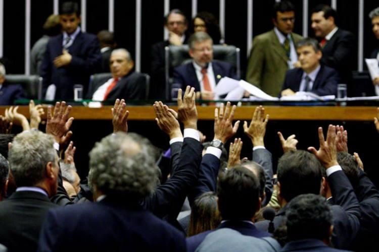 Deputados levantam os braços durante votação do novo salário mínimo, no plenário da Câmara