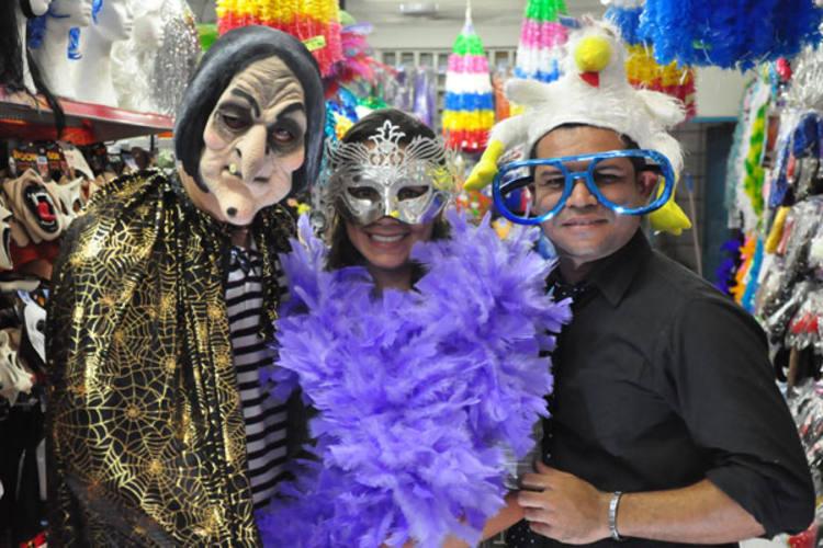 Clientela se diverte enquanto escolhe fantasia para baile. Festas particulares são a maior demanda das lojas