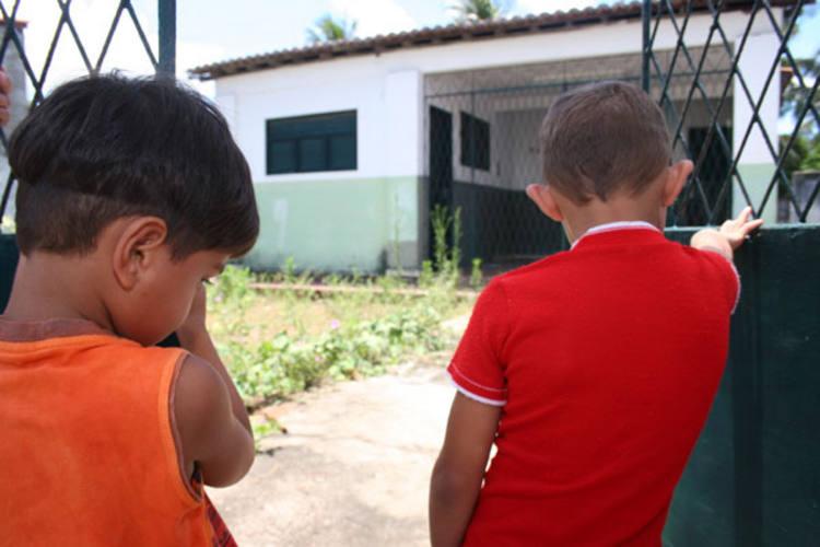 Do lado de fora, Josaias, 4 anos, e Josias, 6 anos, se contentam em olhar o mato que cobre a área de entrada do CMEI Teotônio Canaa, em Igapó. Nos últimos dois anos, o centro não funcionou e até a quarta-feira, 16, não havia nem sinal de que as aulas um dia serão retomadas por ali.