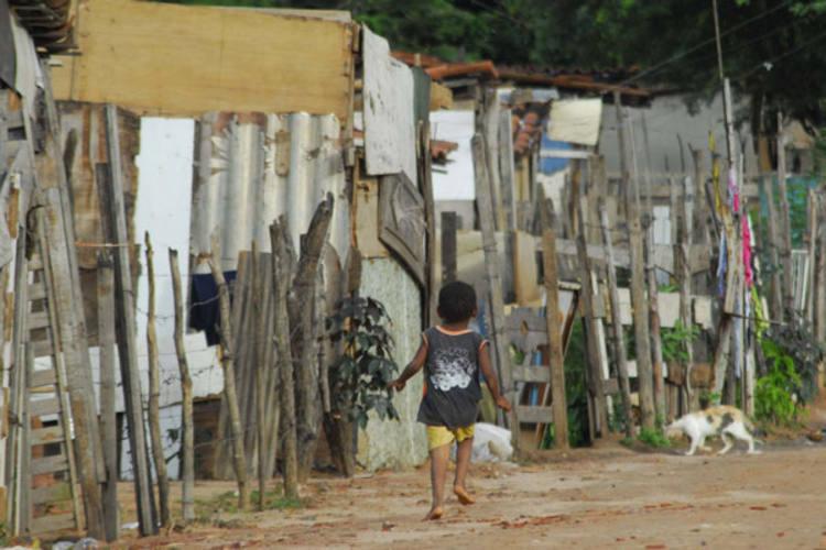 Na Favela do Planalto, a criança brinca em meio aos barracos