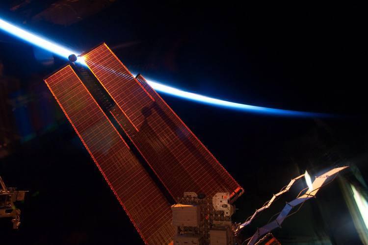 Astronautas da Endeavour fotografam anoitecer na Estação Orbital. No horizonte, o contorno da Terra