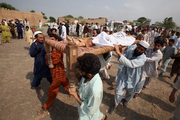 Paquistaneses levam corpo de sunita morto na explosão de uma bomba em região onde atua o Taleban